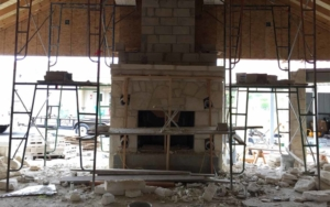 Front view of a fireplace being constructed with stones