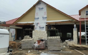 Front view of a home being constructed with tyvek on the sides
