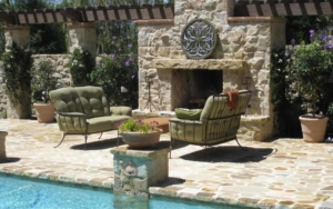 Poolside fireplace with a set of chairs and small table