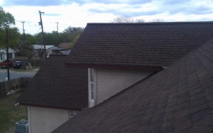 View of a new roof with dark maroon colored shingles