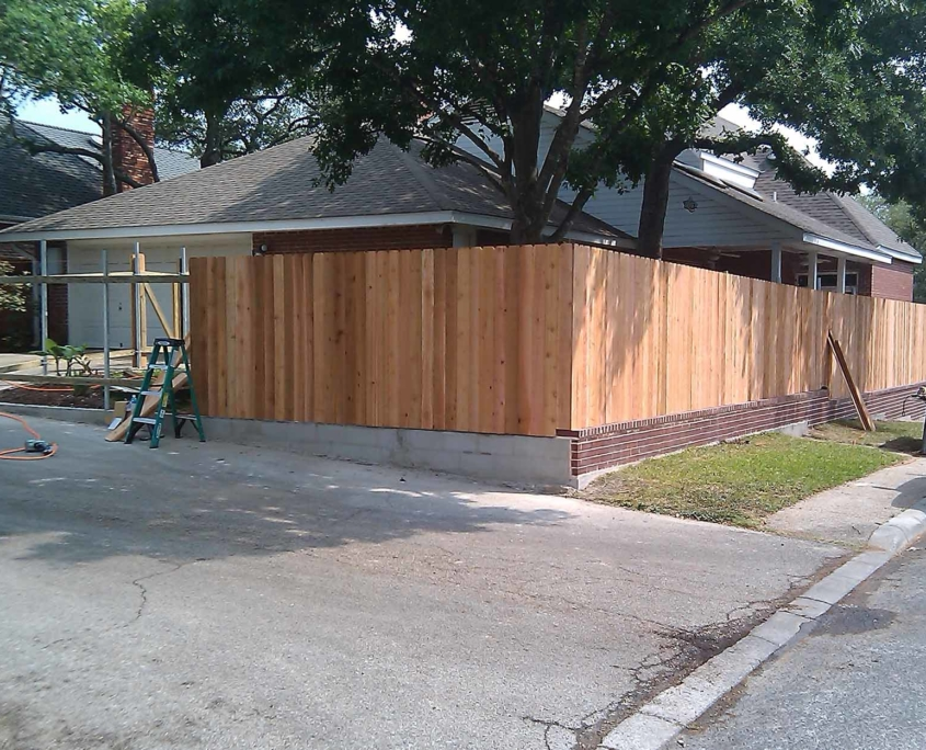 Wooden fence being constructed along the side of a house